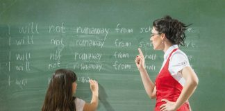 Teacher standing at the board with student writing