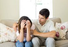 Husband consoling distraught wife on sofa