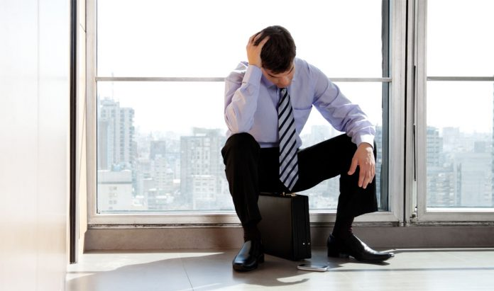 Tensed man in tie sitting on his breifcase with his hand on his head, frustrated in career