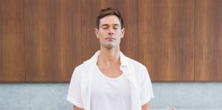 Man meditating in white clothes