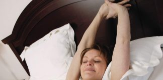 Woman streching her hands on the bed, sleeping concept