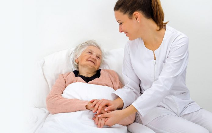 Woman sitting next to an old lady who is bed ridden, compassion