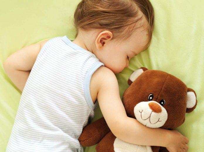 A child sleep with teddy bear