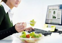 woman eating salad on her work desk