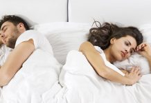 couple lying on bed facing opposite directions