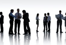 silhoutte of people standing and talking to each other in groups, networking
