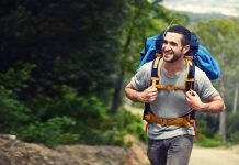 Smiling man walking with a haversack / travel concept