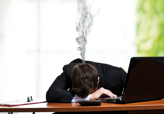 man on office desk with head down / burdened with emotions