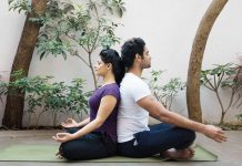 Couple sitting cross legged with backs touching, doing couple yoga