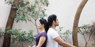 Couple sitting cross legged with backs touching, doing couple yoga