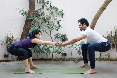 Couple doing the chair pose / Yoga