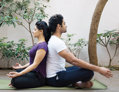 Couple sitting in the partner breathing pose of yoga