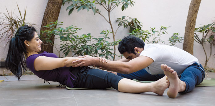 Couple doing the partner forward fold pose of yoga