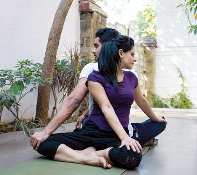 Couple doing the partner twist pose of yoga