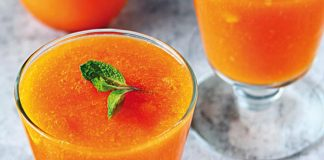 orange drink in glass with mint leaf
