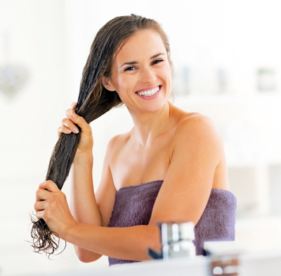 Woman oiling her hair