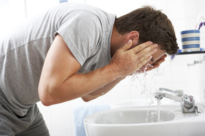 Man washing his face using a cleanser