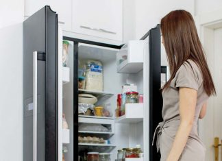 Woman opening a refrigerator which is organised neatly