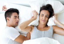 Man snoring in sleep where woman is getting irritated