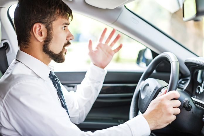 man wearing a tie is frustrated driving car, seems to be complaining