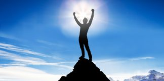 Silhouette of a victorious man on top of a mountain