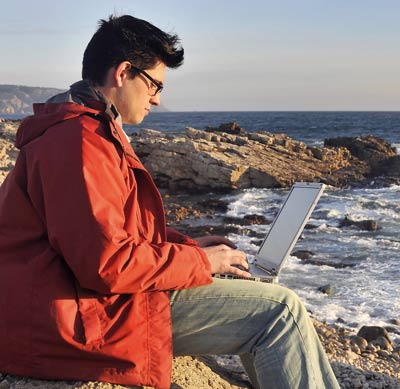 Man working on his laptop sitting on the sea shore