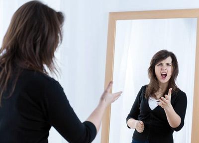 Woman looking at the mirror and shouting to herself