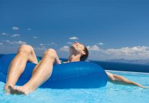 Man enjoying in the beach sitting on the floats