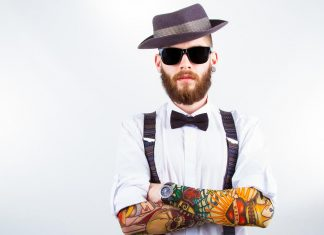 Man wearing hat and bow with solourful tattoo on arms