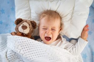 toddler crying bitterly on bed, with a teddy bear next to him