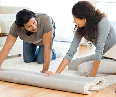 Man and woman putting a new carpet at home