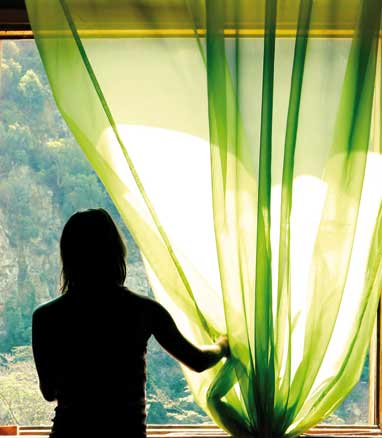 Woman opening the curtain to let sunrays come inside her home