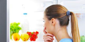 Woman peeping inside the frdige, wondering what to eat