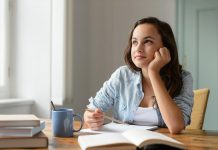Student teenage girl in love studying at home daydreaming