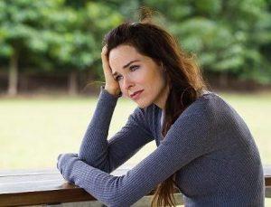 Sad depressed woman sitting outdoors / menopause