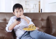Kid watching TV while eating junk food french fries, screen time