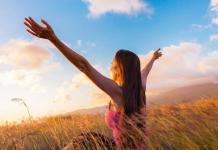 Girl raising arms towards beautiful glowing sunshine / emptiness and love