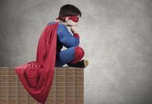 child in superman costume with cape / super-achieving child