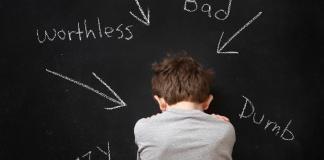 distressed boy against blackboard with negative labels