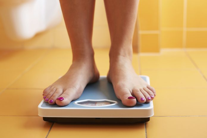 Feet of a lady on a bathroom scale / weight loss concept