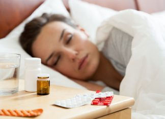 woman sleeping with many pills on her bedside table