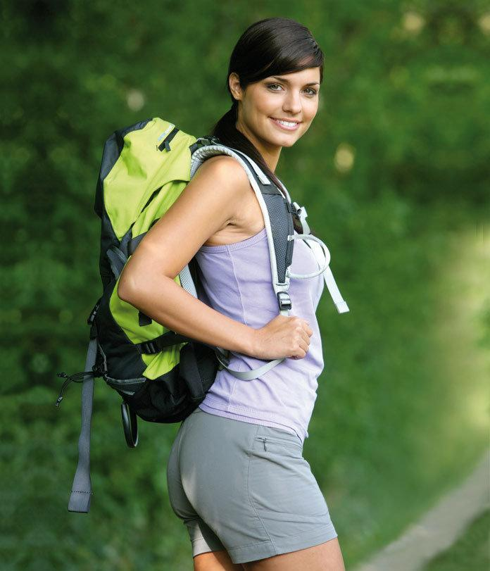 A pretty young woman traveller with bagpack in nature / travel