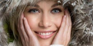 woman wearing snow cap smiling holding her cheeks