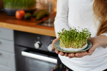 lady holding pot whole of microgreens