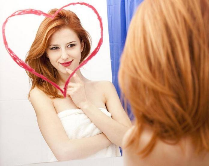 Self-love concept: Girl looking in the mirror smiling with heart shape encircling her reflection