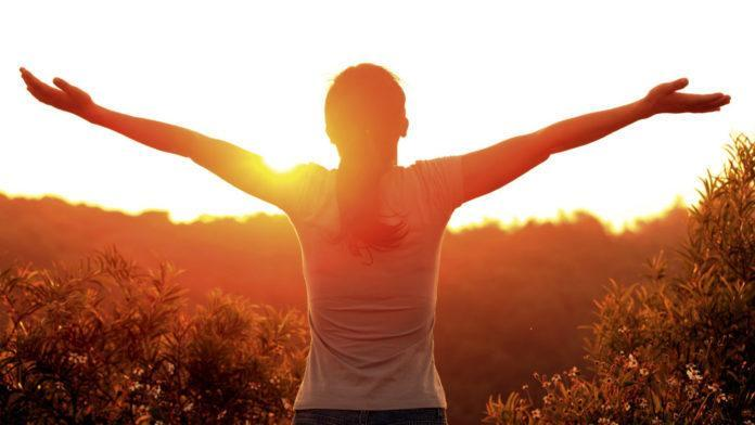 woman arms stretched, sunshine vitamin