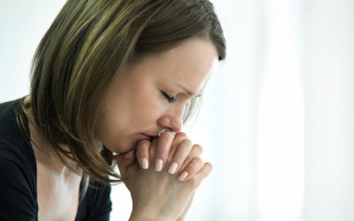 sad woman closes eyes in a gesture of prayer