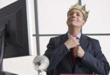 Businessman wearing a crown sitting at desk, arrogance