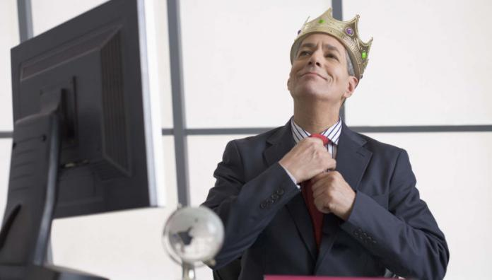 Businessman wearing a crown sitting at desk, arrogance