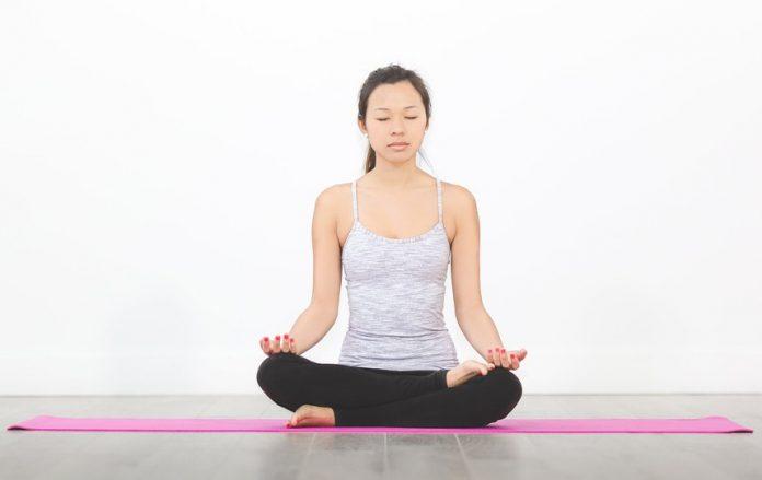 woman sitting on yoga mat in meditation